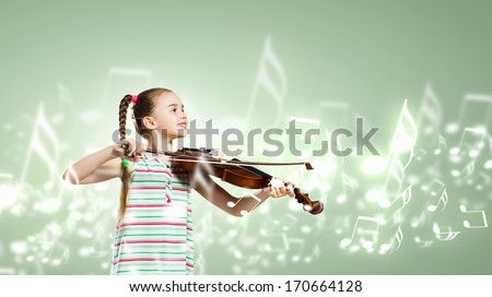 Image of cute girl playing violin against green background - stock photo