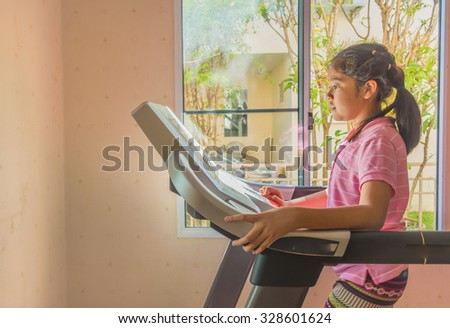 image of Cute girl running treadmill on day time for background usage. - stock photo