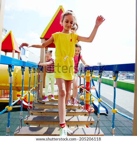 Image of cute girls having fun on playground outdoors  - stock photo