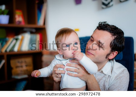 Image of cute little daughter in young dad's hands. Father and baby girl outdoor. Dad feeds child lunch in cafe - stock photo