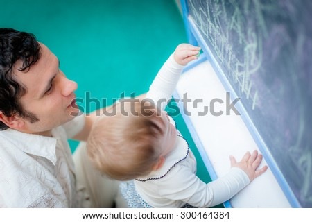 Image of cute little daughter with her young dad. Father and baby girl outdoor. Teacher tells  child on chalkboard - stock photo
