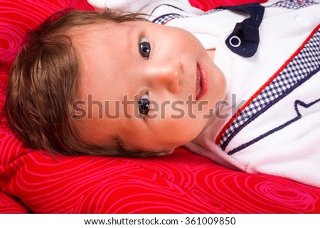 Image of cute newborn boy smiling, closeup portrait of adorable child  on red background. - stock photo