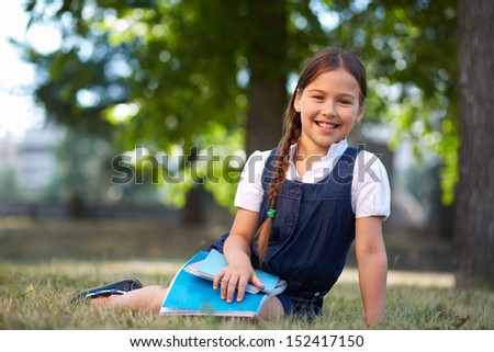 Image of cute schoolgirl with copybooks in summer park