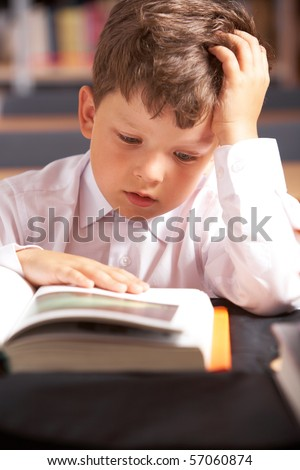 Image of cute schoolkid reading book in the library - stock photo