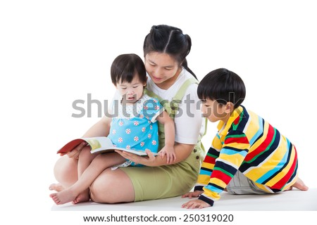 Image of cute young female with two little asian children reading a book together, daughter sitting on the lap, son sitting on the floor, happy family concept, isolated on white background - stock photo