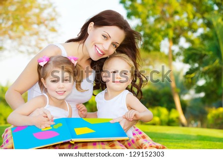 Image of cute young female with two little children read book outdoors, cheerful mother and two pretty kids sitting down on  backyard and enjoying spring nature, daycare, loving family concept