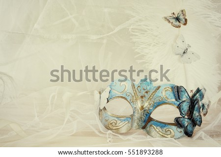 Image of delicate blue elegant venetian mask next to pearls in front of white tulle background. Filtered photo