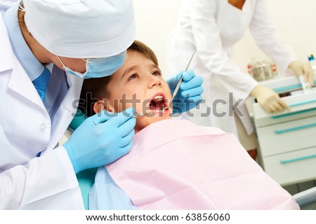 Image of dental examining being given to little boy by dentist - stock photo