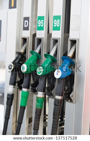 Image of detail of hoses of petrol pump at a gas station, selective focus - stock photo