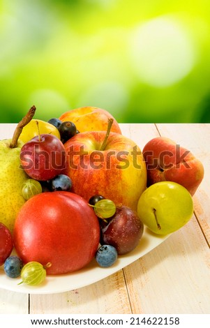 image of different fruits on a plate on a blurred background - stock photo