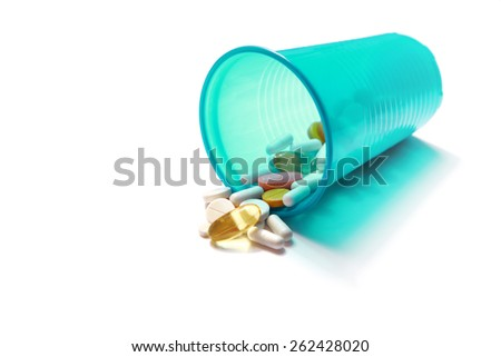 Image of different pills spilling out of a plastic glass - stock photo