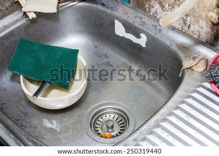 Image of dirty ceramic bowl with scouring pad in dish sink before cleaning - stock photo