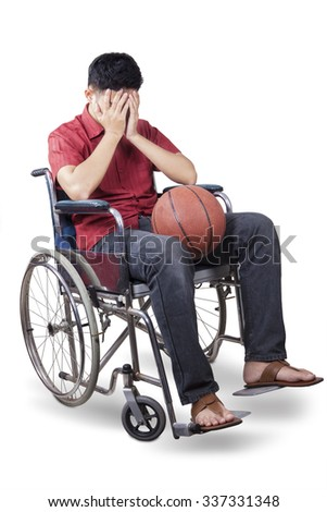 Image of disabled and sad basketball player sitting on the wheelchair while holding a ball, isolated on white background - stock photo