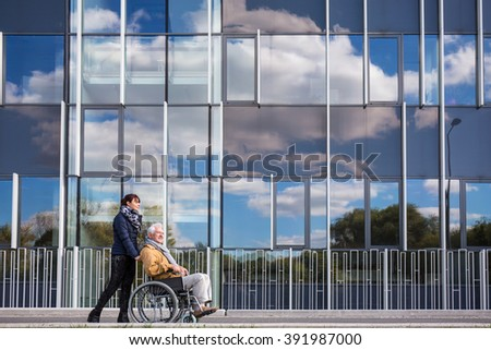 Image of disabled grandfather and his helpful grandchild - stock photo