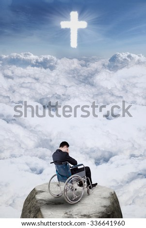 Image of disabled man sitting on wheelchair and looks sad at the cliff with a cross on the sky - stock photo
