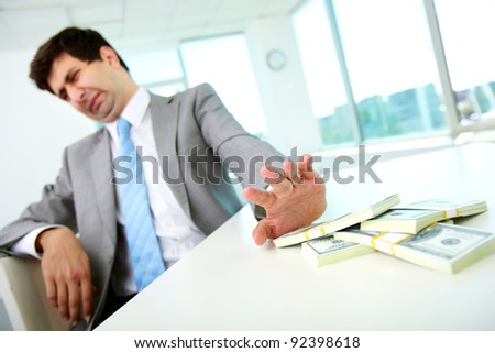 Image of disgusted male employee moving dollar bills away and refusing to take bribe - stock photo