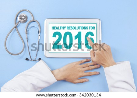 Image of doctor hand using tablet to write healthy resolution for 2016 on the screen - stock photo