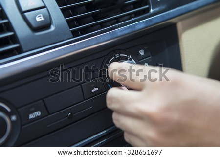 Image of driver hand set the air conditioner button in the car and change the temperature