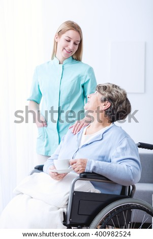 Image of elderly female on wheelchair with carer