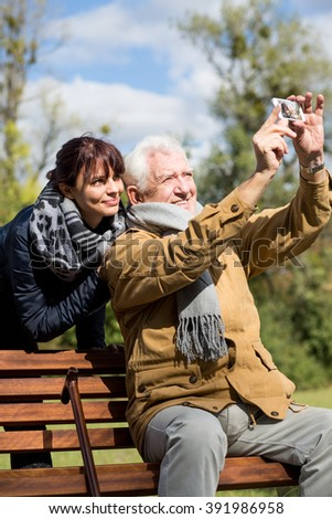 Image of elderly man taking photo with his granddaughter - stock photo