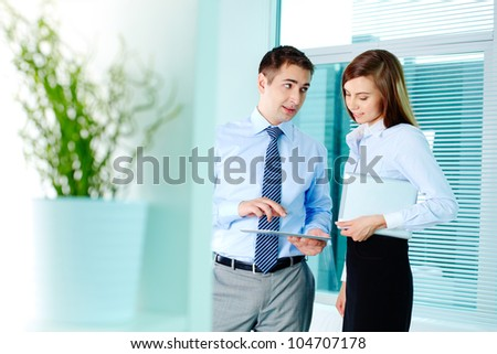 Image of elegant businessman explaining his plan to pretty colleague in office - stock photo