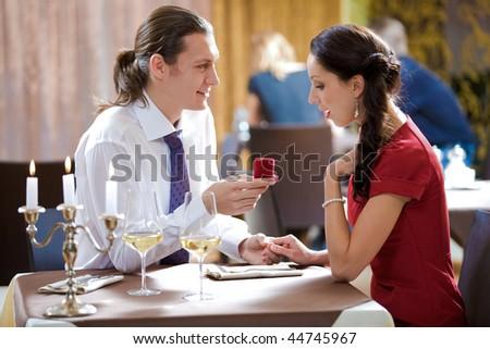 Image of elegant man making proposal to beautiful woman in restaurant during romantic dinner - stock photo