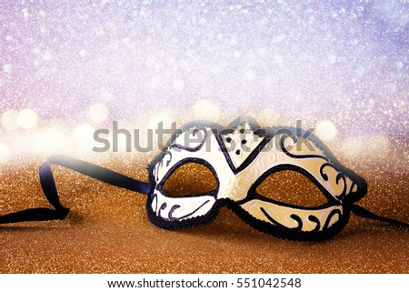 Image of elegant venetian mask on gold glitter background
