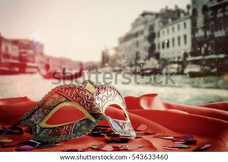 Image of elegant venetian mask on red silk fabric in front of blurry Venice background. Glitter overlay