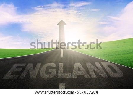 Image of empty asphalt road with word of England and arrow upward at the end of a road