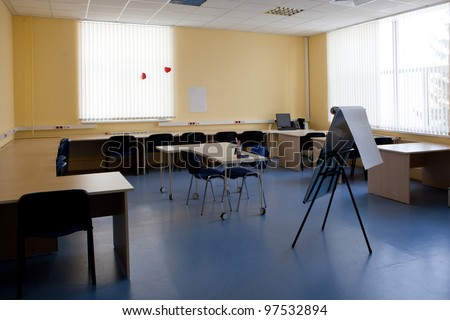 image of empty classroom with tables and chairs - stock photo