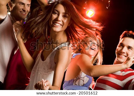 Image of energetic girl looking at camera while dancing on background of her friends