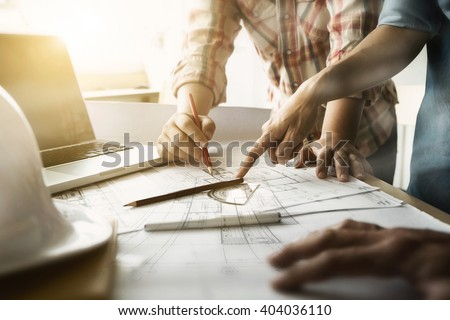 Image of engineer meeting for architectural project. working with partner and engineering tools on workplace vintage tone. - stock photo