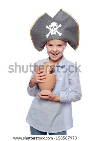 Image of European cute little girl in pirate hat holding a broken old amphora isolated on white Halloween/Beautiful smiling child dressed as a pirate with a broken amphora - stock photo