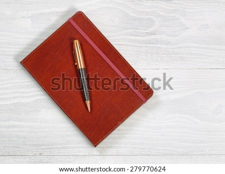 Image of executive notepad with pen on rustic white wood with plenty of copy space.  - stock photo