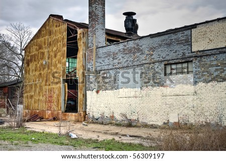 Image of exterior of abandoned warehouse with destroyed metal and brick walls. - stock photo