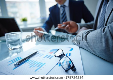 Image of eyeglasses and financial documents at workplace with businessmen discussing ideas near by - stock photo