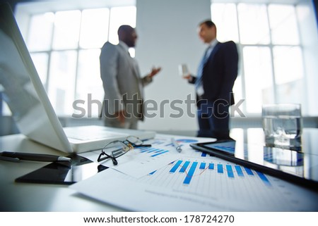 Image of eyeglasses, glass of water, pen, laptop, touchpads and financial documents at workplace with businessmen communicating on background