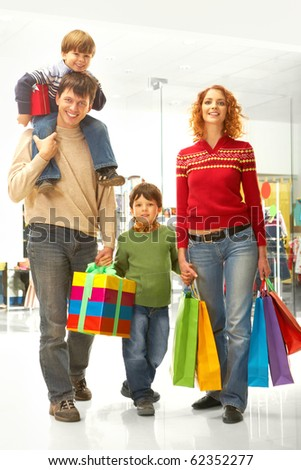 Image of family carrying bags and box before Christmas time - stock photo