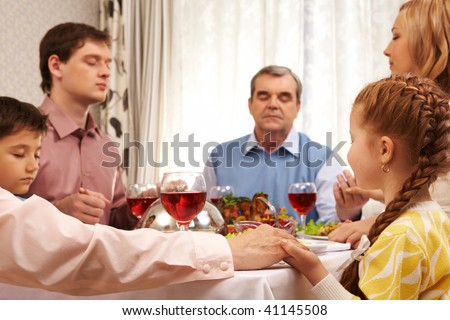 Image of family members praying at festive table while holding each other by hands - stock photo