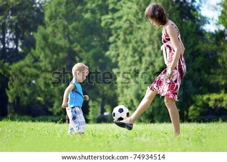 Image of family, mother and son playing ball in the park.