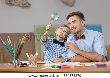 Image of father and son with magnifier - stock photo