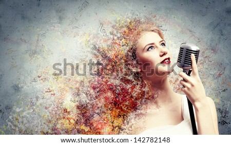 Image of female blond? singer holding microphone against color background - stock photo