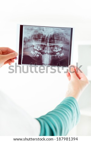 Image of female doctor holding and looking at x-ray of teeth