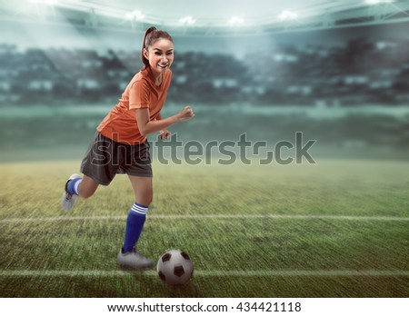 Image of female football player dribbling ball on the stadium
