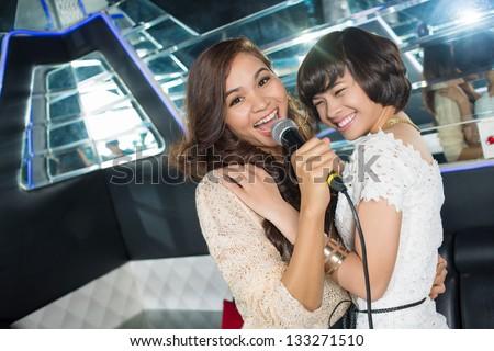 Image of female friends enjoying nightlife in the karaoke bar - stock photo