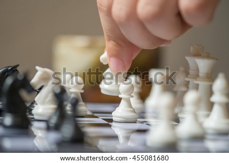 Image of female hand is playing chess. - stock photo