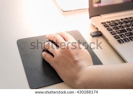 Image of female hands click computer mouse. Selective focus - stock photo