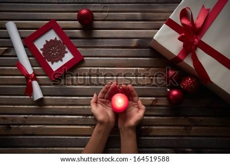 Image of female hands holding burning candle surrounded by Christmas symbols - stock photo