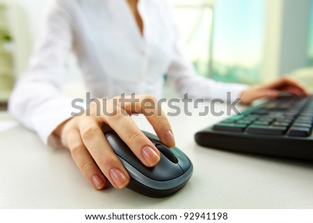 Image of female hands pushing keys of a computer mouse and keyboard - stock photo