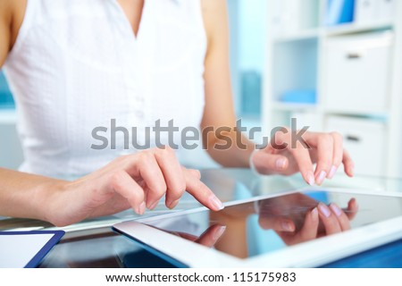 Image of female hands touching screen of digital tablet